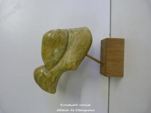 Beeld van Braziliaans speksteen op een houten sokkel.