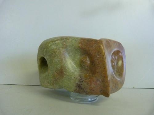Een beeld van Rood Indiaas Speksteen op een glazen sokkel