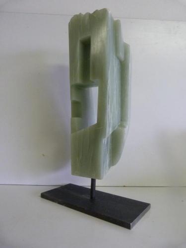 Een beeld van Groen Iraans Speksteen op een stalen sokkel