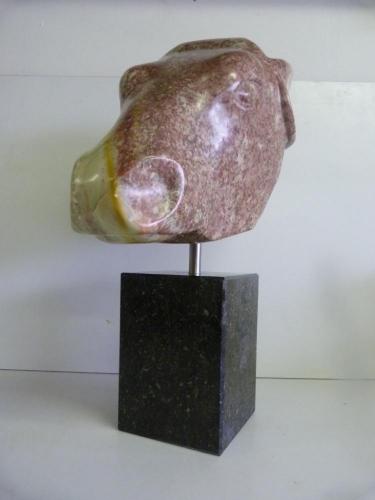 Een beeld van Rood Indiaas Speksteen op een hardstenen sokkel