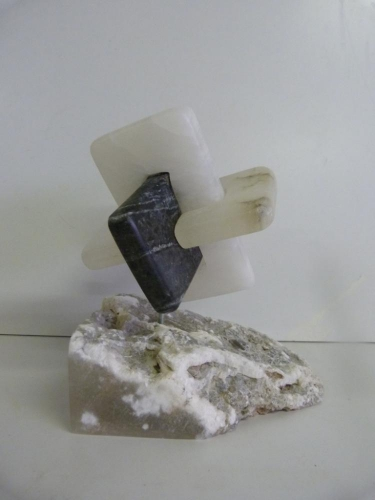 Een beeld van een combinatie van Zwart en Wit albast op een sokkel van Caramel albast
