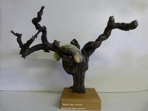 Een beeld van Spaanse wijnrank met daarin verwerkt een stuk Mexicaanse speksteen op een houten sokkel