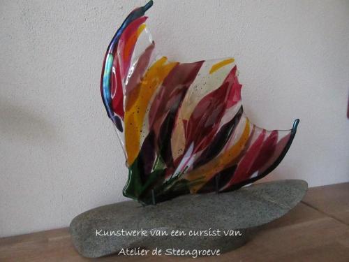Kunstwerk gemaakt van Glas Fushion op een tot beeld vormgegeven serpentijnen sokkel