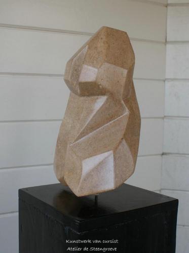 Een beeld van Rode Indiaas speksteen op een houten sokkel