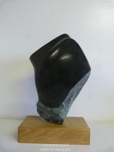 Een beeld van Zwarte Indiaas speksteen op een houten sokkel