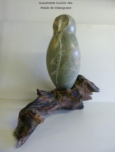 Een beeld van Opaal Serpentijn op een stuk Kienhout