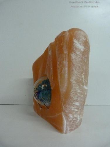 Een beeld van Oranje Seleniet met een glazen bal in het midden