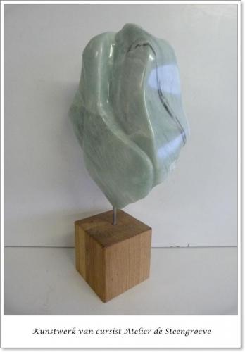 Een Beeld van groene Iraans speksteen op een hardstenen sokkel