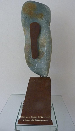 Beeld van Serpentijn met een oor van corten staal en hij staat op een corten stalen sokkel